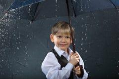 Glimlachende jongen die zich onder paraplu in regen bevindt stock afbeeldingen