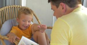 Glimlachende Jongen die Zijn Vader Reading een Boek luisteren stock footage