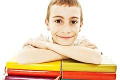 Glimlachende jongen met gekleurde schoolboeken op de lijst stock foto's