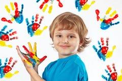 Glimlachende jongen met geschilderde handen op achtergrond van handdrukken Royalty-vrije Stock Foto