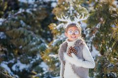 Glimlachende jongen met grappige geweitakken van een hert Het concept van de vakantie stock afbeeldingen