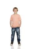 Glimlachende jongen met jeans status Stock Afbeelding