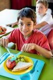Glimlachende jongen met klasgenoten die maaltijd hebben stock afbeeldingen