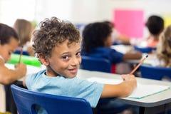 Glimlachende jongen met klasgenoten in klaslokaal stock foto