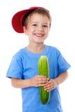 Glimlachende jongen met komkommer stock foto's