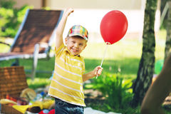 Glimlachende jongen met rode baloon Stock Fotografie