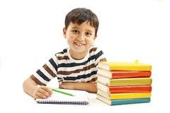 Glimlachende jongen met schoolboeken op de lijst stock afbeeldingen