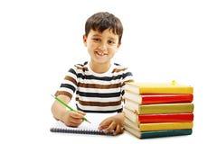 Glimlachende jongen met schoolboeken op de lijst stock foto's