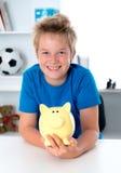 Glimlachende jongen met spaarvarken Royalty-vrije Stock Afbeeldingen