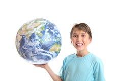 Glimlachende jongen met wereld in palm van zijn handen stock foto's