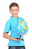 Glimlachende jongen in toevallige holdingsbol in handen Royalty-vrije Stock Afbeeldingen