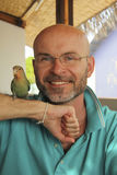 Glimlachende kale mens met een baard met een papegaai Stock Foto