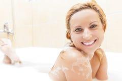 Glimlachende Kaukasische Blonde vrouw die Badkuip met Schuim nemen Het glimlachen Gelaatsuitdrukking Stock Afbeeldingen