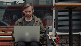 Glimlachende Kaukasische mens die in sociaal netwerk met zijn vriend via laptop computer herschrijven terwijl het rusten in bakke stock videobeelden
