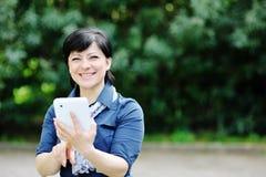 Glimlachende Kaukasische vrouw die tabletcomputer met behulp van Stock Fotografie