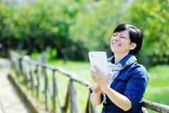 Glimlachende Kaukasische vrouw die tabletcomputer met behulp van Royalty-vrije Stock Afbeeldingen