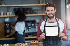 Glimlachende kelner die digitale tablet tonen bij teller in café stock foto
