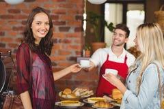 Glimlachende kelner die een koffie dienen aan een klant Royalty-vrije Stock Foto's