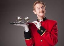 Glimlachende Kelner in rode eenvormig stock afbeeldingen