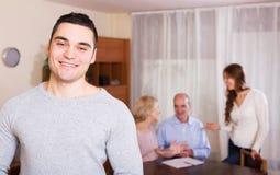 Glimlachende kerel en grote familie met agent bij afstand binnen Royalty-vrije Stock Foto's