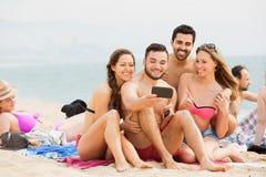 Glimlachende kerels en meisjes die selfie op zee doen Stock Afbeelding