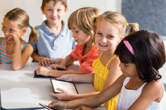 Glimlachende kinderen die digitale tabletten gebruiken stock foto