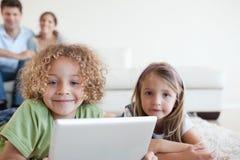 Glimlachende kinderen die een tabletcomputer met behulp van stock foto
