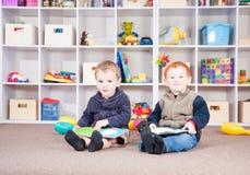 Glimlachende kinderen die jonge geitjesboeken in spelruimte lezen Stock Foto