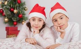 Glimlachende kinderen die met santahoed stellen in studio stock foto's