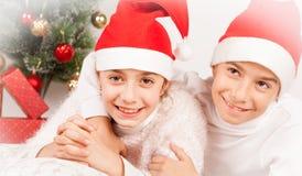 Glimlachende kinderen die met santahoed stellen in studio stock afbeelding