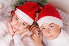 Glimlachende kinderen die met santahoed stellen in studio stock foto