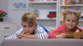 Glimlachende kinderen die op bank liggen en camera, siblings vriendschap bekijken stock videobeelden