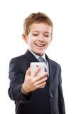 Glimlachende kindjongen die in pak mobiele telefoon houden of slim Stock Fotografie