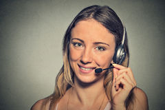 Glimlachende klantenondersteuningsexploitant met hoofdtelefoon op grijze muurachtergrond Stock Foto