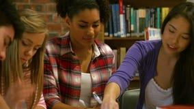 Glimlachende klasgenoten die in bibliotheek bestuderen stock video