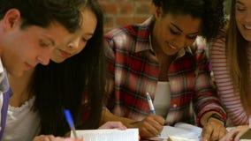 Glimlachende klasgenoten die in bibliotheek bestuderen stock footage