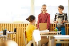 Glimlachende klasgenoten die bij onderbreking babbelen stock foto