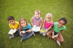 Glimlachende klasgenoten die in gras en het houden van boeken zitten royalty-vrije stock fotografie