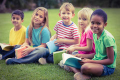 Glimlachende klasgenoten die in gras en het houden van boeken zitten stock foto's