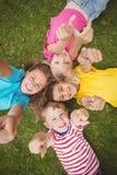 Glimlachende klasgenoten die in gras liggen en aan camera richten royalty-vrije stock afbeeldingen