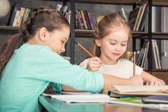 Glimlachende klasgenoten die thuiswerk samen in bibliotheek doen royalty-vrije stock afbeeldingen
