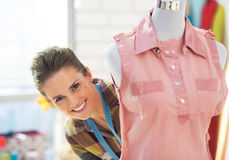 Glimlachende kleermakersvrouw die uit van ledenpop kijken Royalty-vrije Stock Foto's