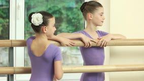 Glimlachende kleine ballerina's die zich bij staaf bevinden stock footage