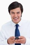 Glimlachende kleinhandelaar die zijn cellphone houdt Royalty-vrije Stock Afbeeldingen