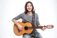 Glimlachende knappe jonge mens met gitaar het zingen in microfoon Stock Foto's