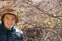 Glimlachende knappe jonge mens in openlucht in bos royalty-vrije stock fotografie