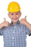 Glimlachende knappe Kaukasische tienerjongen in een gele bouwvakker Het gelukkige kind maken beduimelt omhoog gebaar en het bekij stock fotografie