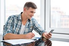 Glimlachende knappe mens die en mobiele telefoon schrijven met behulp van Stock Foto