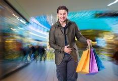 Glimlachende knappe mens met het winkelen zakken Royalty-vrije Stock Afbeeldingen