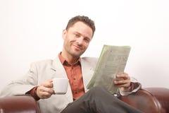 Glimlachende knappe mens met krant en kop van koffie - portret stock foto